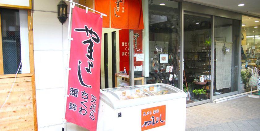 唐人町商店街にある天ぷら・蒲鉾 やまよしの外観です。赤地の暖簾、のぼりには「やまよし」と書いてあります。店頭には白い冷蔵庫が置いてあります。