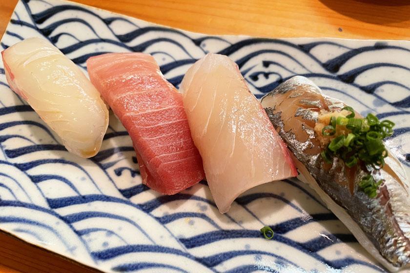 西公園商工連盟の鮨処佐々庄の料理です。白地に青い波の模様の皿に、握り寿司が4貫あります