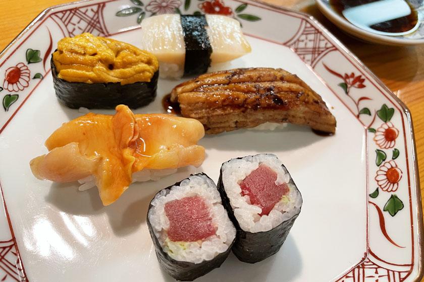 西公園商工連盟の鮨処佐々庄の料理です。陶器の皿に握り寿司が4貫、巻き寿司が2切れあります